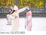 Little adorable girl with her mother skating on ice-rink. Стоковое фото, фотограф Дмитрий Травников / Фотобанк Лори