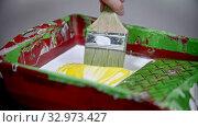 Купить «A person mixing white and yellow colors in the paint tray using a brush», видеоролик № 32973427, снято 3 июня 2020 г. (c) Константин Шишкин / Фотобанк Лори