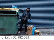 Купить «Bearded bum searching food in trashcan on street», фото № 32982083, снято 26 октября 2019 г. (c) Tryapitsyn Sergiy / Фотобанк Лори