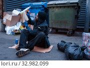 Купить «Dirty drunk beggar lies in garbage at the trashcan», фото № 32982099, снято 26 октября 2019 г. (c) Tryapitsyn Sergiy / Фотобанк Лори