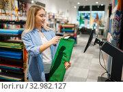 Купить «Woman at cash register sells fabric, textile store», фото № 32982127, снято 8 ноября 2019 г. (c) Tryapitsyn Sergiy / Фотобанк Лори