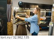 Купить «Seamstress with fabric at mannequin, textile store», фото № 32982135, снято 8 ноября 2019 г. (c) Tryapitsyn Sergiy / Фотобанк Лори