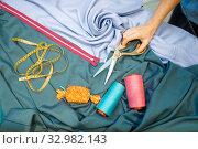 Купить «Seamstress hand with scissors and fabric, top view», фото № 32982143, снято 8 ноября 2019 г. (c) Tryapitsyn Sergiy / Фотобанк Лори