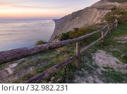 Купить «A fence of tree trunks on the edge of a cliff on a rocky sea coast», фото № 32982231, снято 6 октября 2018 г. (c) Иванов Алексей / Фотобанк Лори