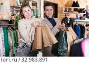 Купить «Smiling couple is satisfied of purchases and standing with package», фото № 32983891, снято 12 марта 2018 г. (c) Яков Филимонов / Фотобанк Лори