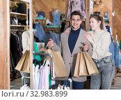 Купить «Smiling couple is satisfied of purchases and standing with package», фото № 32983899, снято 12 марта 2018 г. (c) Яков Филимонов / Фотобанк Лори