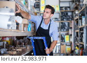 Купить «master is standing on the stairs near the shelves with boxes», фото № 32983971, снято 26 июля 2017 г. (c) Яков Филимонов / Фотобанк Лори