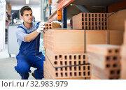 workman is calculating bricks before selling. Стоковое фото, фотограф Яков Филимонов / Фотобанк Лори