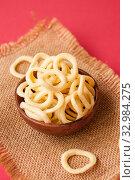Купить «Chips onion rings in a clay Cup on a napkin on a red background», фото № 32984275, снято 10 августа 2019 г. (c) Катерина Белякина / Фотобанк Лори