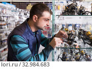 Fisherman customer choosing new baitcasting reel. Стоковое фото, фотограф Яков Филимонов / Фотобанк Лори