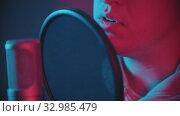 Купить «A man rapping through the pop-filter in the microphone», видеоролик № 32985479, снято 4 апреля 2020 г. (c) Константин Шишкин / Фотобанк Лори
