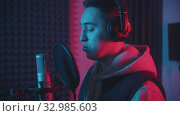 Купить «A man in headphones rapping through the pop-filter in the microphone - studio in neon lighting», видеоролик № 32985603, снято 4 июля 2020 г. (c) Константин Шишкин / Фотобанк Лори