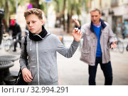 Купить «Frowning teenager gesturing enough while man reprimanding him», фото № 32994291, снято 6 апреля 2020 г. (c) Яков Филимонов / Фотобанк Лори