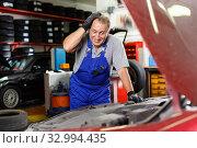 Купить «Puzzled male mechanic inspecting broken car and determining scope of work at auto service», фото № 32994435, снято 4 сентября 2018 г. (c) Яков Филимонов / Фотобанк Лори