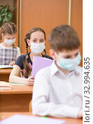 Купить «students wearing mouth mask against virus in class room in school», фото № 32994635, снято 28 января 2020 г. (c) Оксана Кузьмина / Фотобанк Лори