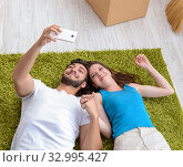Купить «The young family unpacking at new house with boxes», фото № 32995427, снято 10 июля 2017 г. (c) Elnur / Фотобанк Лори
