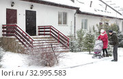 Man helping woman to push back the baby stroller. Snow covered yard of townhouse with blizzard at winter season. Стоковое видео, видеограф Кекяляйнен Андрей / Фотобанк Лори