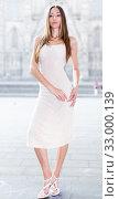 Купить «portrait of young female in sexually ivory midi gown standing in town», фото № 33000139, снято 24 июня 2017 г. (c) Яков Филимонов / Фотобанк Лори