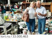 Купить «Pensioner family buys vintage dishes at a flea market», фото № 33000463, снято 11 мая 2019 г. (c) Яков Филимонов / Фотобанк Лори