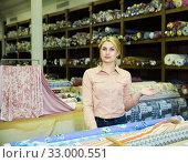 Купить «Female seller of fabric shop showing textiles», фото № 33000551, снято 2 марта 2018 г. (c) Яков Филимонов / Фотобанк Лори