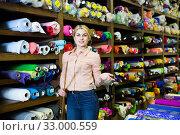 Купить «Saleswoman offering cloth in textile shop», фото № 33000559, снято 2 марта 2018 г. (c) Яков Филимонов / Фотобанк Лори