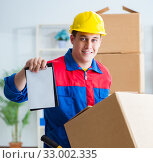 Купить «The young man working in relocation services with boxes», фото № 33002335, снято 30 июня 2017 г. (c) Elnur / Фотобанк Лори