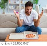 Купить «Man eating pizza having a takeaway at home relaxing resting», фото № 33006047, снято 18 июля 2017 г. (c) Elnur / Фотобанк Лори