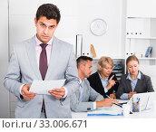 Купить «Irritated businessman in office with working associates», фото № 33006671, снято 1 июля 2017 г. (c) Яков Филимонов / Фотобанк Лори