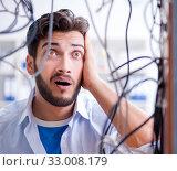 Купить «Electrician trying to untangle wires in repair concept», фото № 33008179, снято 7 июля 2017 г. (c) Elnur / Фотобанк Лори