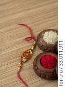 Купить «Indian festival: Raksha Bandhan background with an elegant Rakhi, Rice Grains and Kumkum. A traditional Indian wrist band which is a symbol of love between Brothers and Sisters.», фото № 33011911, снято 27 июля 2018 г. (c) easy Fotostock / Фотобанк Лори