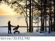 Mother walking with baby stroller in winter sundown, fresh air in nature. Стоковое фото, фотограф Кекяляйнен Андрей / Фотобанк Лори