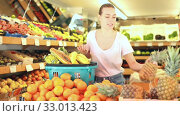 Купить «Cheerful woman standing with full shopping cart during shopping in fruit store», видеоролик № 33013423, снято 26 мая 2019 г. (c) Яков Филимонов / Фотобанк Лори