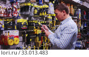 Купить «Portrait of male in hardware store buying goods», видеоролик № 33013483, снято 8 апреля 2020 г. (c) Яков Филимонов / Фотобанк Лори