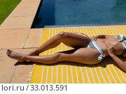 Купить «Young woman relaxing near swimming pool on a sunny day», фото № 33013591, снято 28 ноября 2019 г. (c) Wavebreak Media / Фотобанк Лори