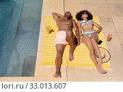 Купить «Young couple relaxing near swimming pool on a sunny day», фото № 33013607, снято 28 ноября 2019 г. (c) Wavebreak Media / Фотобанк Лори