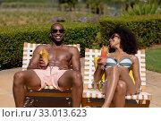 Купить «Young couple relaxing near swimming pool on a sunny day», фото № 33013623, снято 28 ноября 2019 г. (c) Wavebreak Media / Фотобанк Лори