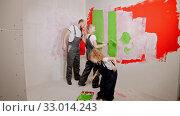 Купить «Family are painting with rollers and brushes the white walls with green paint», видеоролик № 33014243, снято 3 июня 2020 г. (c) Константин Шишкин / Фотобанк Лори