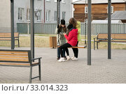 Девушки подросткового возраста сидят на качелях и смотрят в мобильный телефон в зоне отдыха. Редакционное фото, фотограф Светлана Попова / Фотобанк Лори