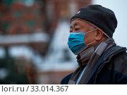 Мужчина в медицинской маске на Красной площади в городе Москве во время эпидемии коронавируса в Китае. Редакционное фото, фотограф Николай Винокуров / Фотобанк Лори