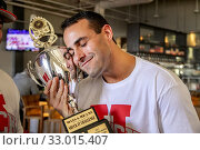A T-shirted male contestant celebrates his team's victory in an oyster-eating contest at a Huntington Beach, CA, restaurant by hugging the trophy. (2019 год). Редакционное фото, фотограф Spencer Grant / age Fotostock / Фотобанк Лори