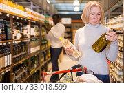 Купить «Attentive woman choosing vegetable oil», фото № 33018599, снято 14 ноября 2019 г. (c) Яков Филимонов / Фотобанк Лори