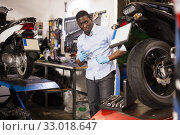 Afro american expert inspects the wheel of a motorcycle. Стоковое фото, фотограф Яков Филимонов / Фотобанк Лори