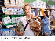 Portrait of positive boy with dog during selecting dry food in petshop, woman on background. Стоковое фото, фотограф Яков Филимонов / Фотобанк Лори