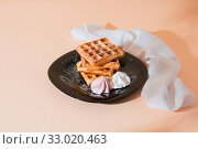 Купить «Sweet delicious dessert, homemade baked goods for breakfast. Belgian European soft waffles on a black plate and meringue», фото № 33020463, снято 30 ноября 2019 г. (c) Светлана Евграфова / Фотобанк Лори