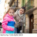 Купить «Angry naughty girl with worried mother outdoors», фото № 33020503, снято 28 мая 2020 г. (c) Яков Филимонов / Фотобанк Лори