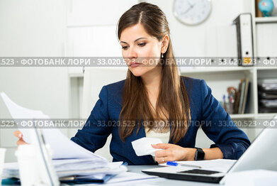 Tired young businesswoman working with documents in office