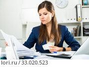 Купить «Tired young businesswoman working with documents in office», фото № 33020523, снято 4 июня 2019 г. (c) Яков Филимонов / Фотобанк Лори