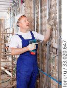 Construction worker using screw gun for aluminum profile mounting at indoors building site. Стоковое фото, фотограф Яков Филимонов / Фотобанк Лори