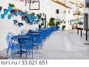 Купить «Mijas Pueblo Blanco, charming small village, picturesque empty street in old town with bright blue tables chairs of local cafe, flower pots hanging on white washed houses walls, Costa del Sol, Spain», фото № 33021651, снято 17 декабря 2019 г. (c) Alexander Tihonovs / Фотобанк Лори