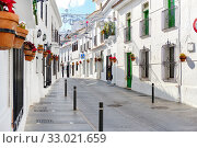 Купить «Mijas white washed street, small famous village in Spain. Charming empty narrow streets with New Year decorations, on houses walls hanging flower pots, sunny day no people. Costa del Sol, Málaga», фото № 33021659, снято 17 декабря 2019 г. (c) Alexander Tihonovs / Фотобанк Лори